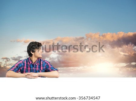 Portrait of young handsome man with blank banner - stock photo