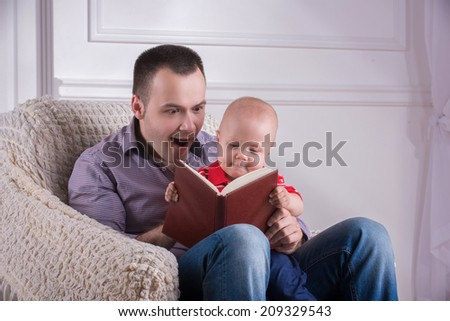 Portrait of young handsome smiling father sitting in cozy armchair with his toddler son reading a book, father is surprised, interior shot - stock photo