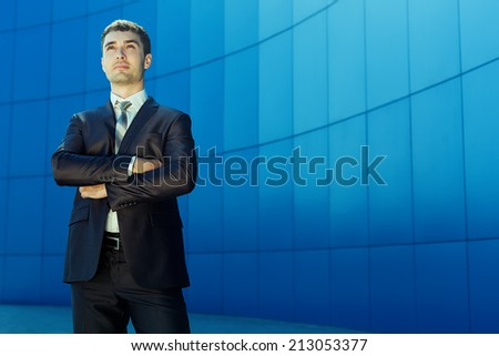 Portrait of young handsome successful business man in suit standing over blue wall. Outdoor. Copy space - stock photo