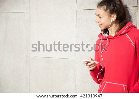 Portrait of young happy beautiful female leaning on gray background while resting after everyday workout. Woman athlete runner taking a break and listening to music using phone app. Copyspace - stock photo