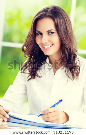 Portrait of young happy brunette businesswoman at office - stock photo