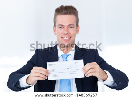 Portrait Of Young Happy Businessman Offering Cheque - stock photo