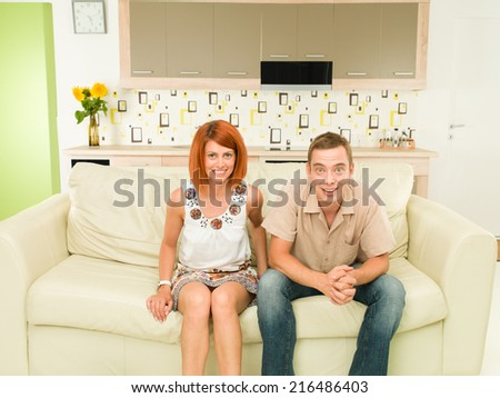 portrait of young happy caucasian couple sitting on sofa, watching tv - stock photo