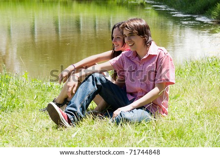 Portrait of young, happy couple against the nature - stock photo