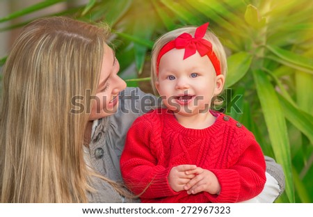 Portrait of young happy family spending leisure time in the park, cheerful mother with pleasure looking on her adorable little daughter, love and happiness concept - stock photo