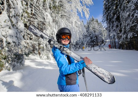 Portrait of young happy female skier on a ski slope in the winter forest on a sunny day. Girl is holding skis on her shoulder smiling and looking towards the camera. Ski resort. Wide angle - stock photo