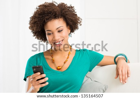 Portrait Of Young Happy Girl Writes a text message At Cellphone - stock photo