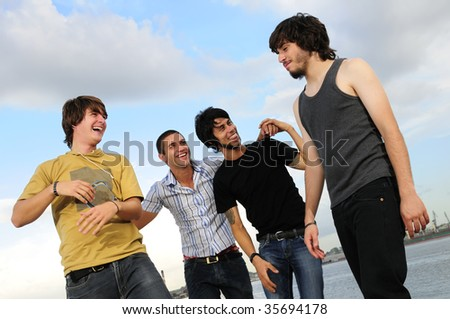 Portrait of young happy group of friends posing outdoors - stock photo