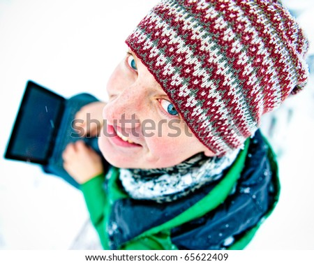 Portrait of young happy handsome man working on his laptop outdoor sitting on bench in winter park - stock photo