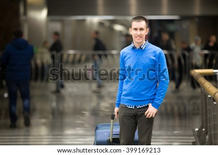 Portrait of young happy handsome travelling man wearing smart casual style clothes walking in modern airport. Cheerful guy travelling with suitcase. Copy space - stock photo