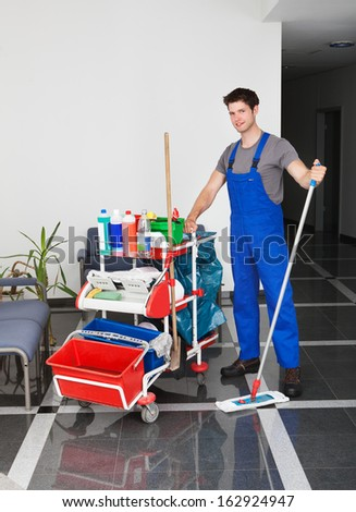 Portrait Of Young Happy Man Standing With Cleaning Equipment In Office - stock photo