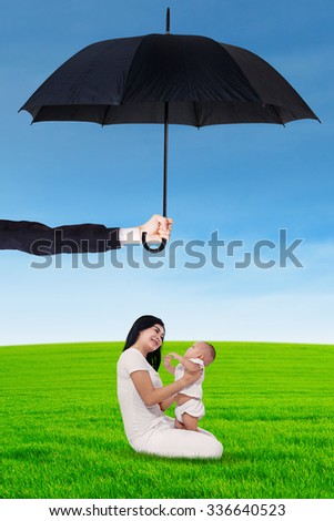 Portrait of young happy mother playing with her daughter on the meadow under umbrella. Life and family insurance concept - stock photo