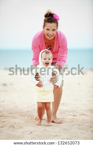 Portrait of young happy mother with child at the beach - stock photo