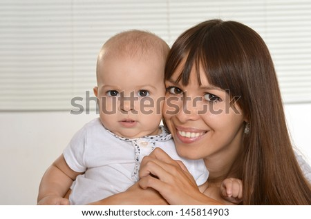 Portrait of young happy mother with her baby on a light background - stock photo