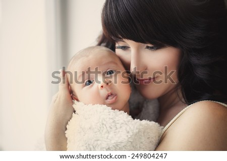 portrait of Young happy mother with her newborn baby lying on bed in home interior. happy mother holding her baby and playing with him indoors. Mother and baby - stock photo
