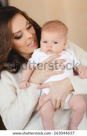 portrait of Young happy mother with her newborn baby on her hands in home interior. happy mother holding her baby and playing with him indoors. Mother and baby - stock photo