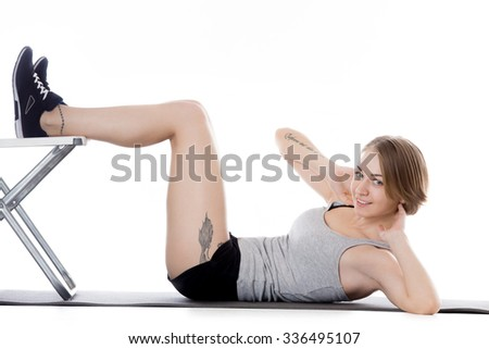 """Portrait of young happy slim beautiful woman working out, warming up, doing abdominal crunches with office chair, French tattoo on her arm translated as """"What woman wants, God wants"""" - stock photo"""