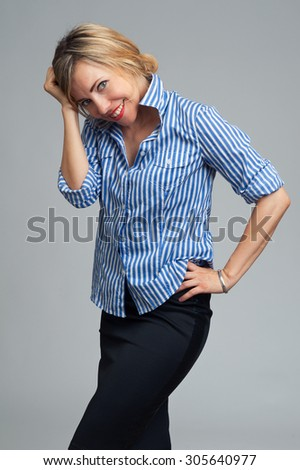 Portrait of young happy smiling business woman over gray background - stock photo