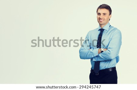 Portrait of young happy smiling businessman, in blue confident business wear, with blank copyspace area for slogan or text message - stock photo