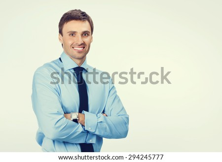 Portrait of young happy smiling businessman in blue confident business wear, with blank copyspace area for slogan or text message - stock photo