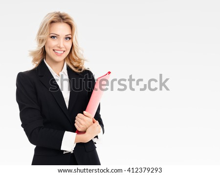 Portrait of young happy smiling businesswoman with red folder, on grey background, with blank copyspace area for text or slogan - stock photo