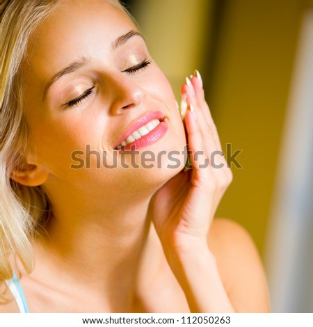Portrait of young happy smiling cheerful beautiful blond woman applying creme, at home - stock photo