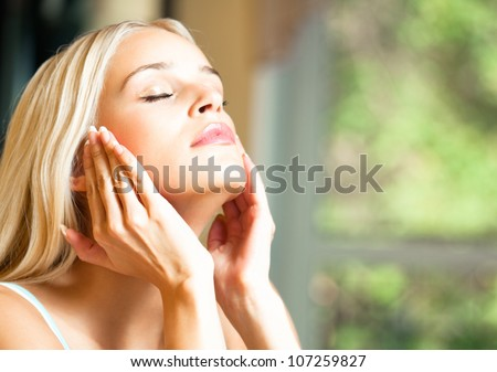 Portrait of young happy smiling cheerful beautiful blond woman applying creme, at home, with copyspace - stock photo
