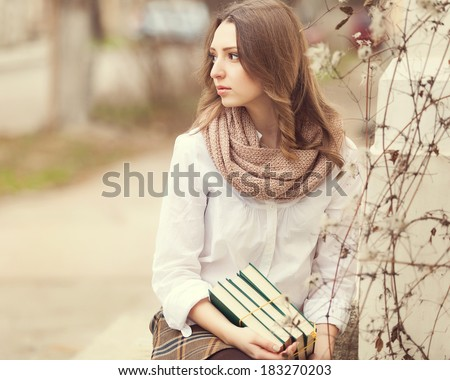 Portrait of young happy smiling cheerful college student in park with a books - stock photo
