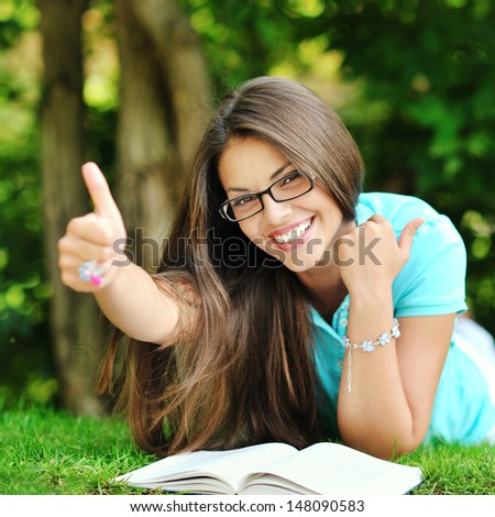 Portrait of young happy smiling cheerful woman in glasses lying in a park and showing thumbs up - stock photo