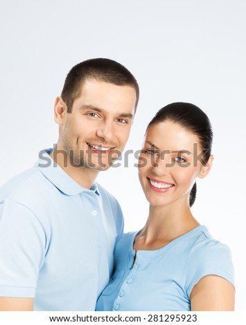 Portrait of young happy smiling couple, with copyspace blank area for text or slogan, over grey background - stock photo