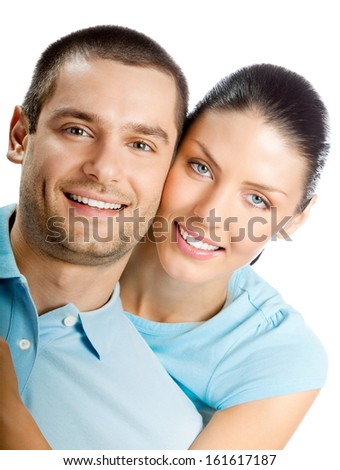 Portrait of young happy smiling embracing attractive couple with copyspace, isolated on white background - stock photo
