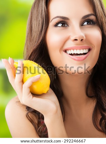 Portrait of young happy smiling lovely woman with lemon, outdoor - stock photo