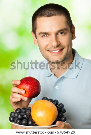 Portrait of young happy smiling man with plate of fruits, outdoors - stock photo