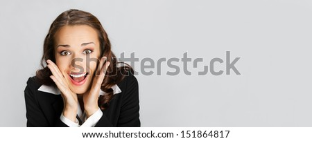 Portrait of young happy smiling surprised business woman, over gray background, with copyspace - stock photo