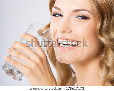 Portrait of young happy smiling woman drinking water, over gray background - stock photo