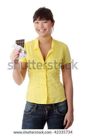 Portrait of young happy smiling woman eating chocolate - stock photo