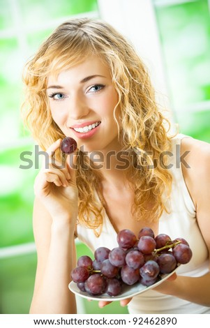 Portrait of young happy smiling woman eating grape, at home - stock photo