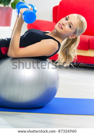 Portrait of young happy smiling woman in sportswear, doing fitness exercise with dumbbell on fit ball, at home - stock photo