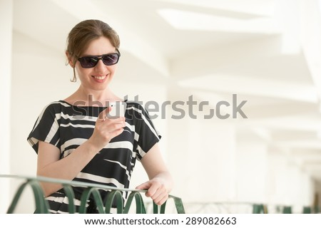 Portrait of young happy smiling woman in sunglasses and black and white summer dress standing in building with white walls, holding cellphone, looking at the screen, using app, messaging - stock photo
