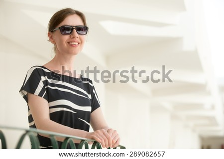Portrait of young happy smiling woman in sunglasses and black and white summer dress standing in a building with white stucco walls, enjoying sunshine - stock photo