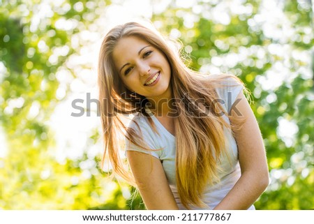 Portrait of young happy smiling woman (teen girl) - outdoor in nature - stock photo