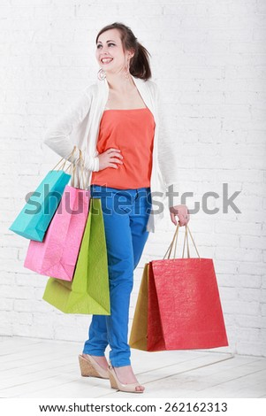 Portrait of young happy smiling woman with shopping bags, isolat - stock photo