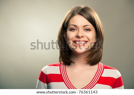 Portrait of young happy woman , big natural smile, beautiful model posing in studio over gray background . Isolated on gray. Light make-up without strong retouching natural skin. - stock photo