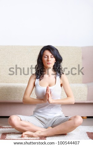 Portrait of young happy woman doing yoga exercise at home - stock photo