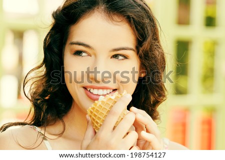Portrait of young happy woman eating ice-cream, outdoor - stock photo