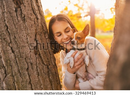 Portrait of young happy woman holding little cute dog in yellow autumn park - stock photo