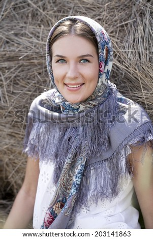 Portrait of young happy woman in blue scarf - stock photo