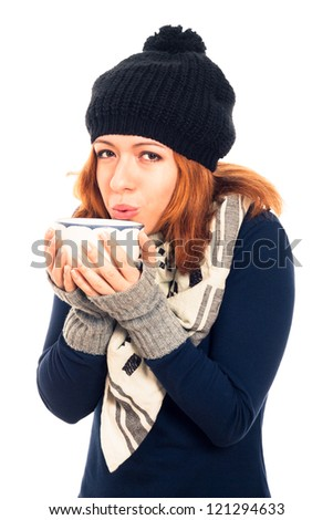 Portrait of young happy woman in winter clothes holding mug with hot drink, isolated on white background. - stock photo