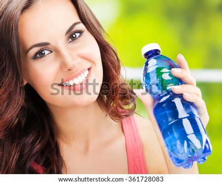 Portrait of young happy woman with bottle of water - stock photo