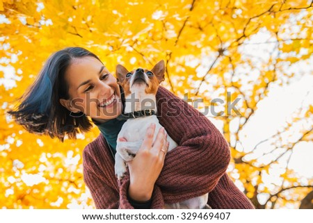 Portrait of young happy woman with little cute dog in autumn park with yellow leaves - stock photo